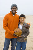Smiling father and son holding soccer ball on beach.  royalty free stock photography