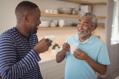 Smiling father and son interacting while having cup of coffee. At home Royalty Free Stock Image