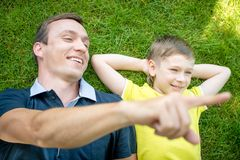 Smiling father and son lying on the grass pointing Royalty Free Stock Image