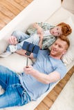 Smiling father and son lying on sofa and taking selfie with smartphone. Family fun at home concept Stock Photo