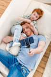 Smiling father and son lying on sofa and taking selfie with smartphone. Family fun at home concept stock photography