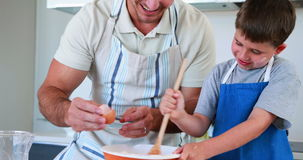 Smiling father and son making a cake together stock footage
