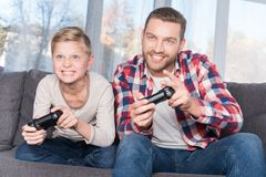 Father and son playing with joysticks. Smiling father and son playing with joysticks together at home Stock Photography
