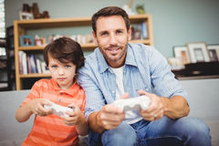 Smiling father and son playing video game Royalty Free Stock Photography