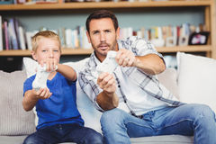 Smiling father and son playing video game while sitting on sofa. At home Stock Photo