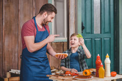 Smiling father and son preparing hot dog together in backyard Royalty Free Stock Photo