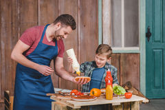Smiling father and son preparing hot dog together in backyard Stock Images