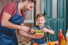 Smiling father and son preparing hot dog together in backyard Royalty Free Stock Photography