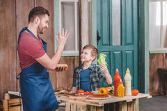 Smiling father and son preparing hot dog together in backyard Stock Image