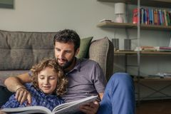Smiling father and son reading a book at home stock image