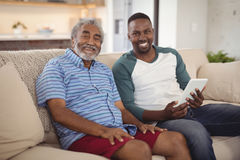 Smiling father and son sitting on sofa with digital tablet in living room stock image