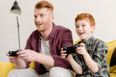 Smiling father and son sitting on sofa and playing with joysticks. At home stock photography