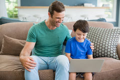 Smiling father and son sitting on sofa using laptop in living room. At home Royalty Free Stock Photo