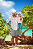 Smiling father and son on summer vacation near the tropical seaside Royalty Free Stock Photo