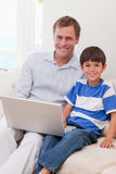 Smiling father and son surfing the internet together Stock Images