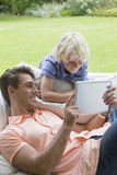 Smiling father and son using digital tablet on outdoor sofa Stock Photo