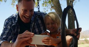 Father and son using digital tablet at playground 4k. Smiling father and son using digital tablet at playground on a sunny day 4k stock footage