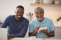 Smiling father and son using laptop and digital tablet in kitchen. Portrait of smiling father and son using laptop and digital tablet in kitchen at home royalty free stock photos