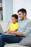 Smiling father and son using laptop on the sofa. In living room Stock Photos