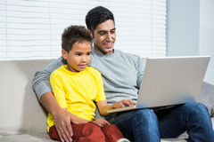 Smiling father and son using laptop on the sofa. In living room Royalty Free Stock Image
