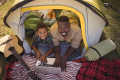 Smiling father and son using laptop in tent Stock Image