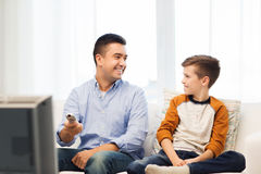 Smiling father and son watching tv at home Stock Photo