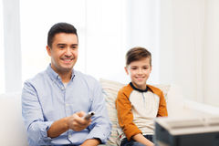 Smiling father and son watching tv at home Royalty Free Stock Photos