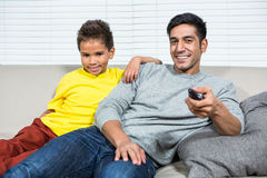 Smiling father and son watching tv on the sofa Stock Images