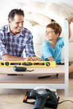 Smiling father and son working in workshop Royalty Free Stock Images