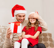 Smiling father surprises daughter with gift box Royalty Free Stock Photo