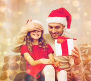 Smiling father surprises daughter with gift box royalty free stock photography