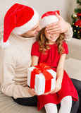 Smiling father surprises daughter with gift box Stock Photography