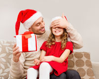 Smiling father surprises daughter with gift box Stock Photos