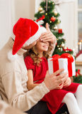 Smiling father surprises daughter with gift box Royalty Free Stock Images
