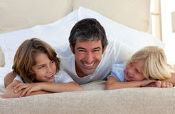 Smiling father talking with his children. Lying on bed at home Stock Photos