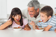Smiling father talking with his children during their breakfast Stock Image