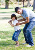 Smiling father teaching baseball to his son Stock Photos