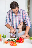 Smiling father teaching daughter to cut vegetable. At home royalty free stock photography
