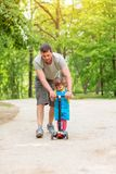 Smiling father teaching his little daughter to ride kid scooter at the park stock photo