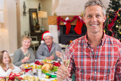 Smiling father toasting at camera in front of his family Stock Image