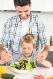 Smiling father tossing salad with his son Stock Image