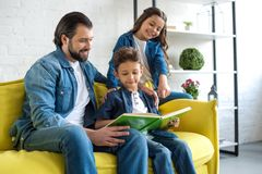 smiling father with two kids reading book together while sitting on couch