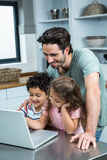 Smiling father using laptop with his children. In kitchen at home stock image