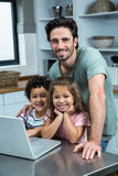 Smiling father using laptop with his children in kitchen. Portrait of smiling father using laptop with his children in kitchen stock photos