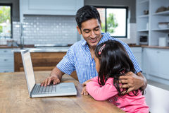 Smiling father using laptop with his daughter Stock Photography