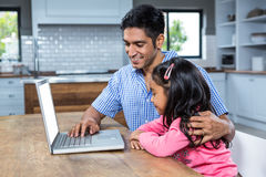 Smiling father using laptop with his daughter Royalty Free Stock Photo
