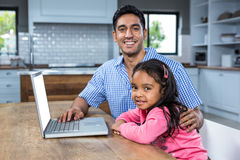 Smiling father using laptop with his daughter Stock Photo