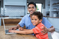 Smiling father using laptop with his son Royalty Free Stock Images