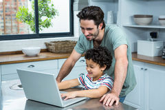 Smiling father using laptop with his son. In the kitchen at home stock image