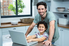 Smiling father using laptop with his son in the kitchen. Portrait of smiling father using laptop with his son in the kitchen at home royalty free stock photos